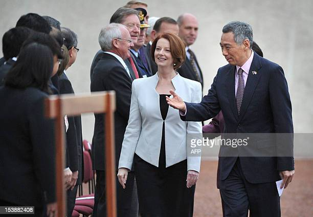 Singapore Prime Minister Lee Hsien Loong introduces Australian Prime Minister Julia Gillard to members of his deligation on the forecourt of...