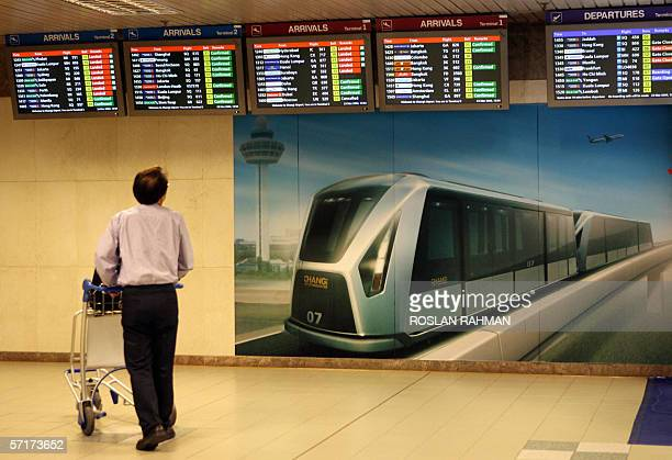 A passenger looks at the flight schedule before boarding a train to Terminal One at the Changi International Airport in Singapore 23 March 2006...