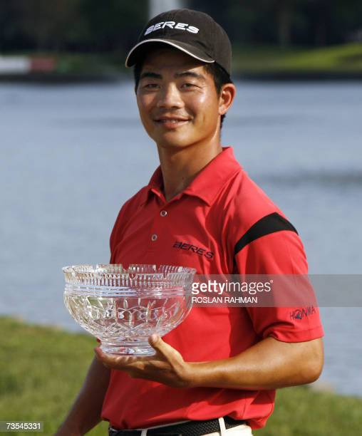 Chinese number one Liang Wenchong holds the trophy after winning against Malaysia's Iain Steel in a playoff during the final round of the 11 million...
