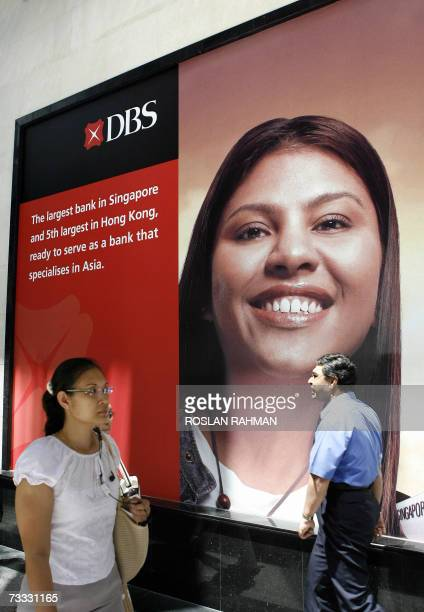People walk past an advertisement for the Development Bank of Singapore in the financial district in Singapore 15 February 2007 Southeast Asia's...