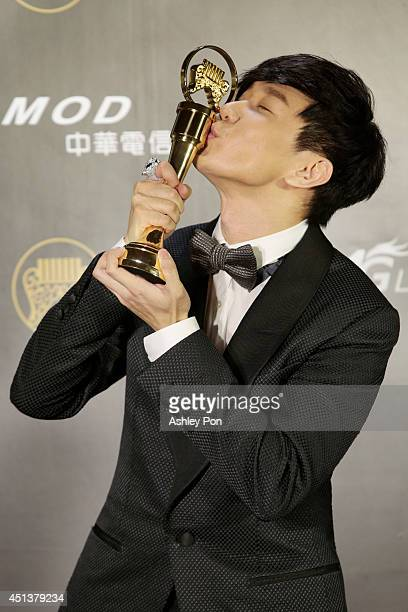 Singapore singer JJ Lin kisses his award for Best Male Mandarin singer at the 25th Golden Melody Awards on June 28 2014 in Taipei Taiwan