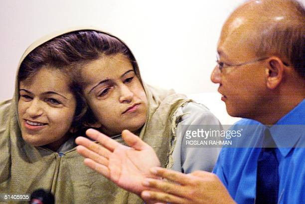 Singaporean neorosurgeon Keith Goh talks to Iranian twin sisters Laleh and Ladan Bijani joined by the head at a press conference at Raffles Hospital...