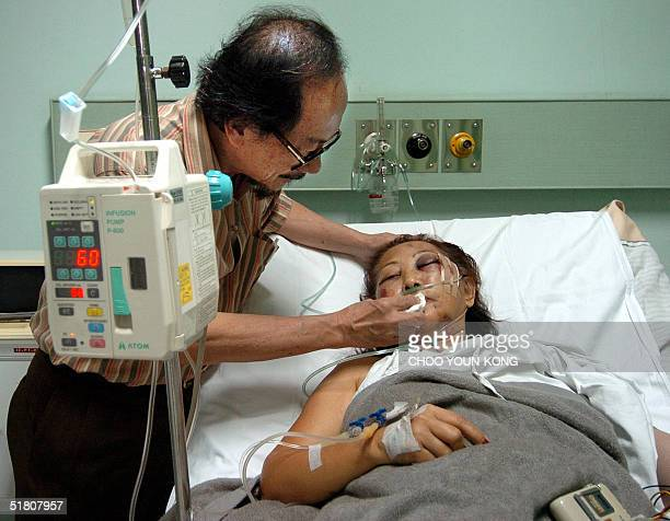 Singaporean Phua Cheng Kit wipes the lips of his wife Maria Phua survivor from a accident of a passenger plane at a hospital in Solo Central Java 01...