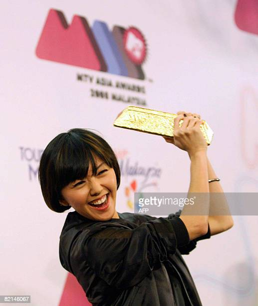 Singaporean pop singer Stefanie Sun smiles as she holds up the MTV Asia Awards trophy during a press conference at Genting Highlands on August 12008...