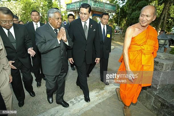 Singaporean President SR Nathan gestures to a Buddhist monk as he walks with Thai Foreign Minister Surakiart Sathirathai and Singapore Ambassador to...