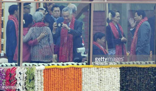 Singaporean Prime Minister Lee Hsien Loong takes a photograph of his wife as Myanmar's civilian leader Aung San Suu Kyi speaks with President of...