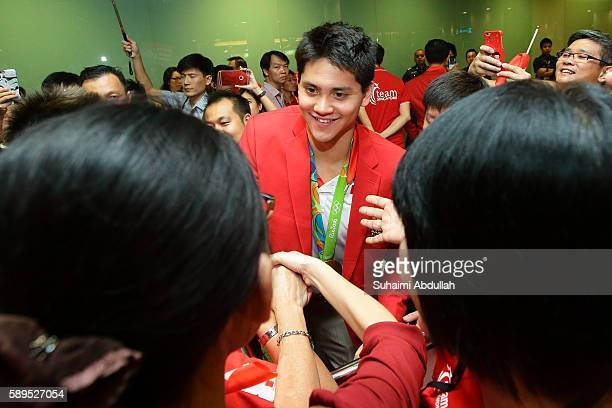 Singaporean swimmer Joseph Schooling greets his fans during a welcome home ceremony at Changi Airport Terminal 3 on August 15 2016 in Singapore...