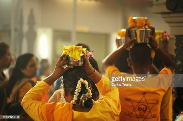 CONTENT] Singaporean Tamil women carry milk pots on their head in a hindu temple at the beginning of the Taipusam pilgrimage honouring Murugan