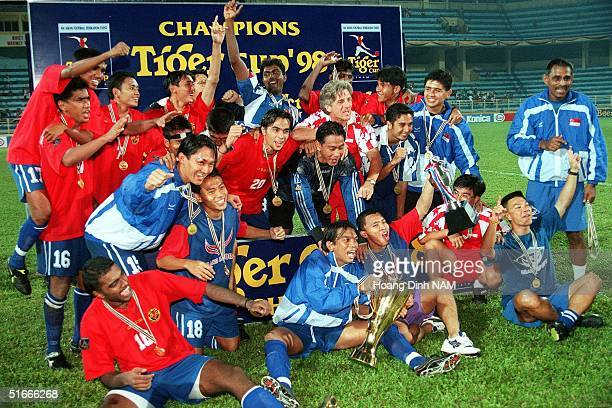 Singaporean team players shouts 'We are the champion' as they pose with their trophy after winning the Tiger Cup's final against Vietnam 05 September...