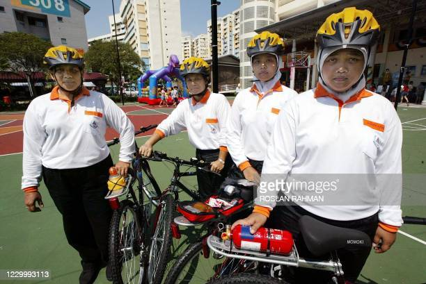 Singaporean volunteers of the Women On Wheel team, a community-based self-help group by Community Safety & Security Programme pose next to their...