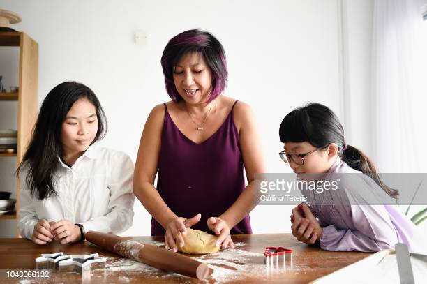 singaporean woman rolling out cookie dough with her nieces - aunt stock pictures, royalty-free photos & images