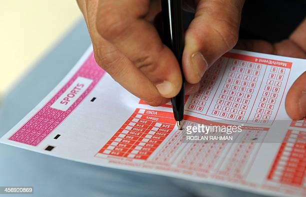 SingaporeFblAsiaSINENGBritaincrimegamblingFOCUS by Bhavan JAIPRAGAS This illustration taken on December 10 2013 shows a person filling out a sports...