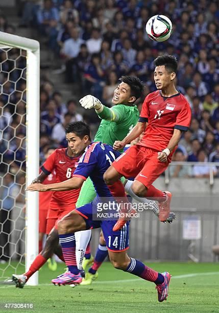 Singapore's goalkeeper Mohamad Izwan Bin Mahbud and his teammate defender Muhammad Nazrul Bin Ahmad Nazari fight for the ball against Japan's forward...