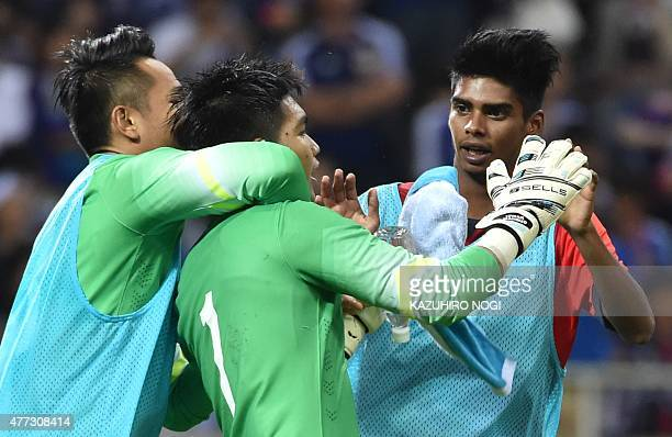 Singapore's goalkeeper Mohamad Izwan Bin Mahbud is congratulated by his teammates following the 2018 FIFA World Cup football qualifying match between...