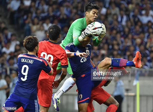 Singapore's goalkeeper Mohamad Izwan Bin Mahbud makes a save above Japan's defender Tomoaki Makino during the 2018 FIFA World Cup football qualifying...
