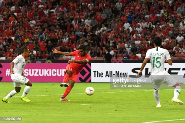 Singapore's midfielder Harris Harun kicks for a goal against Indonesia's defender Ricky Fajrin Saputra during the AFF Suzuki Cup 2018 football match...