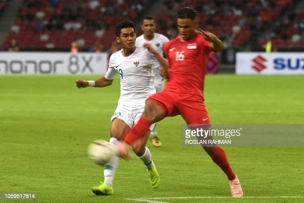 Singapore's midfielder Irfan Fandi fights for the ball with Indonesia's midfielder Septian David Maulana during the AFF Suzuki Cup 2018 football...