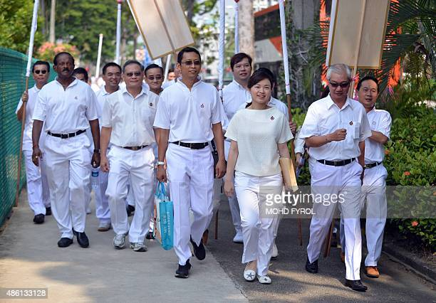 Singapore's People's Action Party member Tin Pei Ling walks with party members as they visit a nomination centre to file documents on Nomination Day...