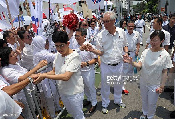 Singapore's People's Action Party members Fatimah Lateef Edwin Tong former prime minister Goh Chok Tong and Tin Pei Ling greet supporters at a...