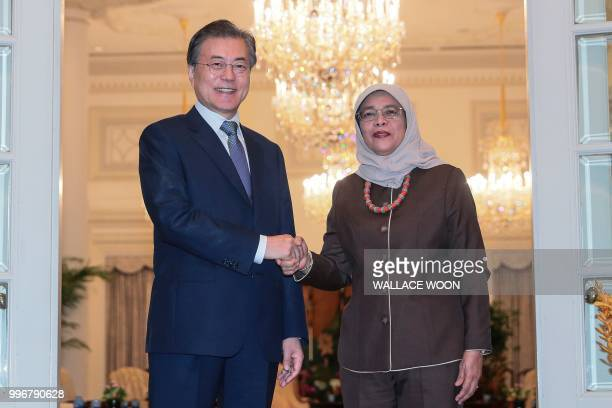 Singapore's President Halimah Yacob shakes hands with South Korea's President Moon Jaein during a meeting at the Istana presidential palace in...