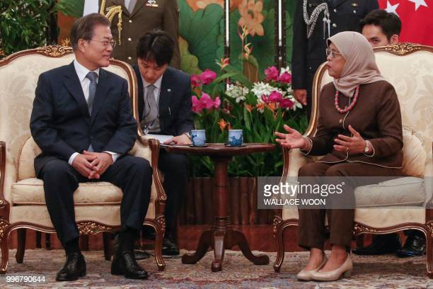 Singapore's President Halimah Yacob speaks with South Korea's President Moon Jaein during a meeting at the Istana presidential palace in Singapore on...