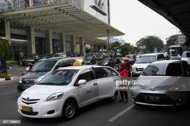 SingaporeSEAsiatransportInternettaxiMalaysiaIndonesiaFOCUS by Bhavan Jaipragas In this photograph taken October 8 2014 a passenger boards a taxi at...