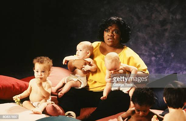 Singer actress and star of TV's Gimme A Break Nell Carter poses with a handful of babies during a 1991 Los Angeles California filming of a public...