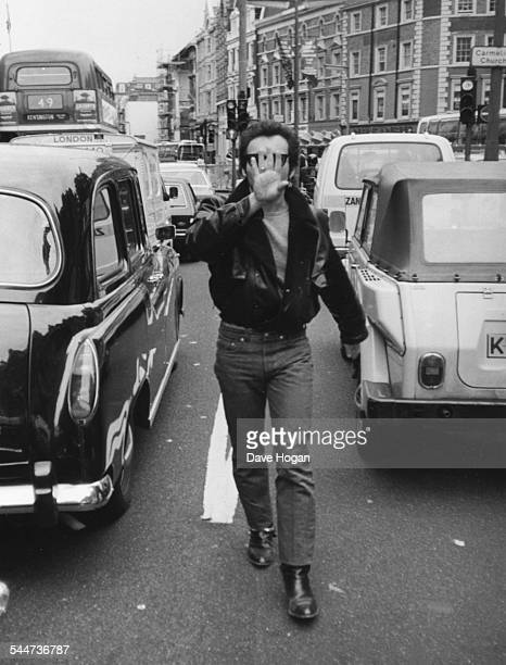 Singer Adam Ant covering his face as he angrily attempts to confront photographer Dave Hogan after getting out of a taxi August 16th 1982