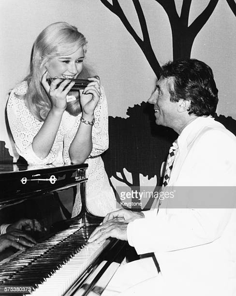 Singer Albert Raisner playing the piano as he serenades 'Miss France' winner Brigitte Konjovic his new fiance circa 1978