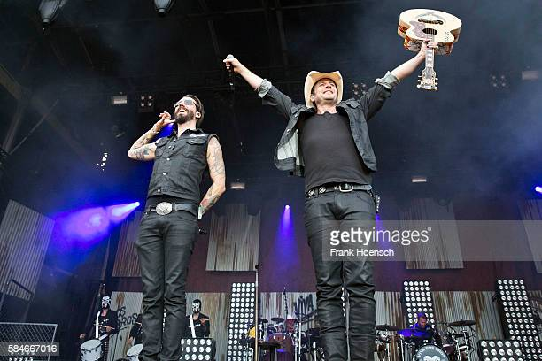 Singer Alec Voelkel and Sascha Vollmer of the German band The Boss Hoss perform live during a concert at the Zitadelle Spandau on July 29 2016 in...