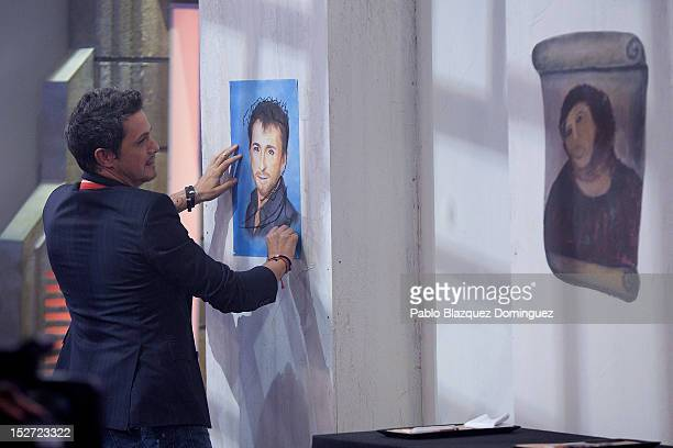 Singer Alejandro Sanz paints next to an 'Ecce Homo' picture during 'El Hormiguero' Tv Show at Vertice Studio on September 24 2012 in Madrid Spain