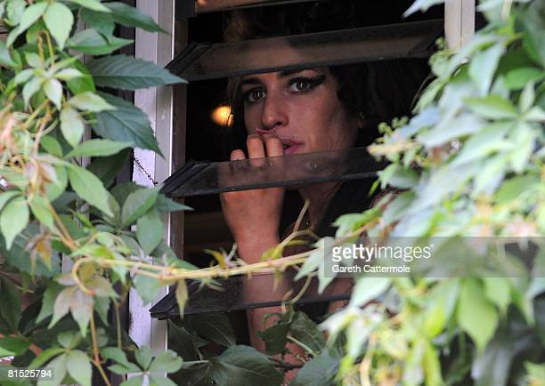 Singer Amy Winehouse eats sweets and chats to local kids out the window of her North London home on June 11 2008 in London England