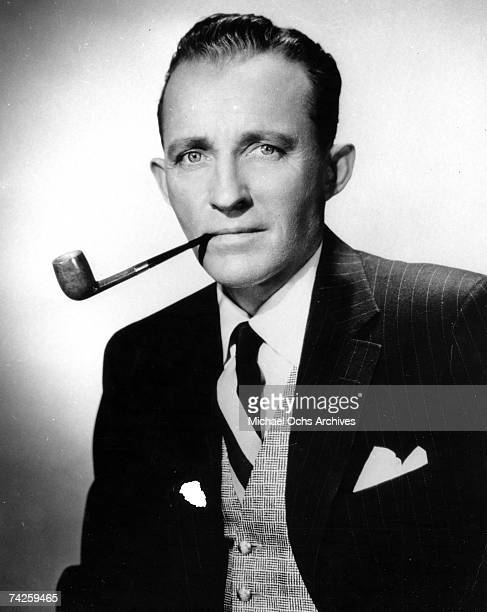 Singer and Actor Bing Crosby poses for a portrait smoking a pipe circa 1955