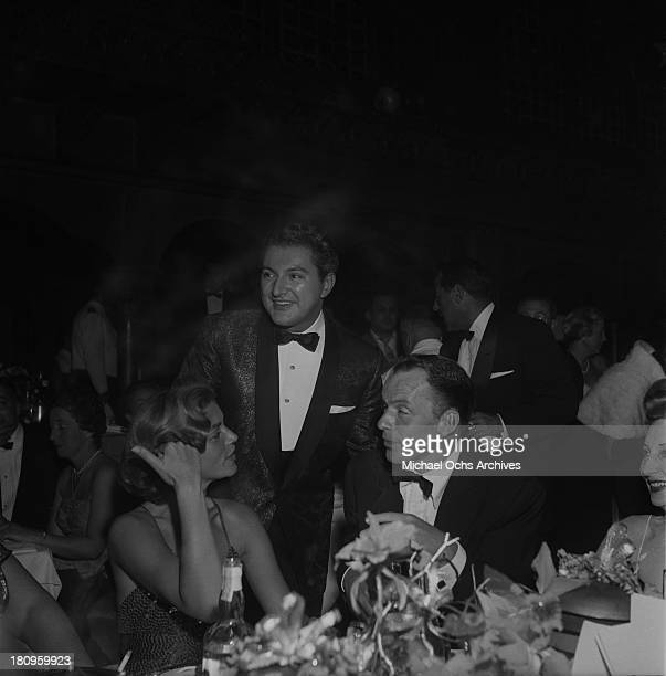 Singer and actor Frank Sinatra and actress Lauren Bacall chat with pianist Liberace at the premiere party for 'A Star is Born' on September 29 1954...