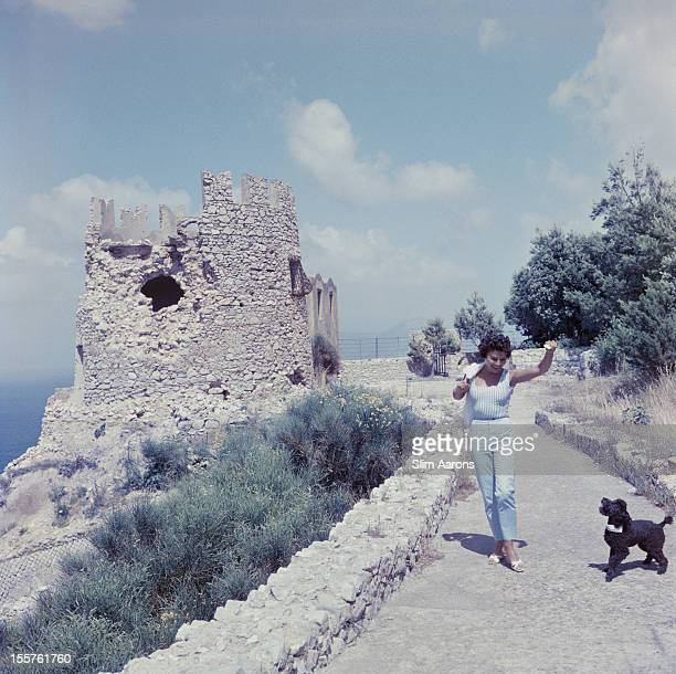 Singer and actress Caprice Chantal passes a ruined fortification while walking a small black poodle on the island of Capri, Italy, in July 1958.
