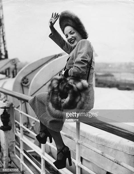 Singer and actress Carmen Miranda sitting on the hand rail on the deck of the SS America as she arrives in Southampton April 20th 1948