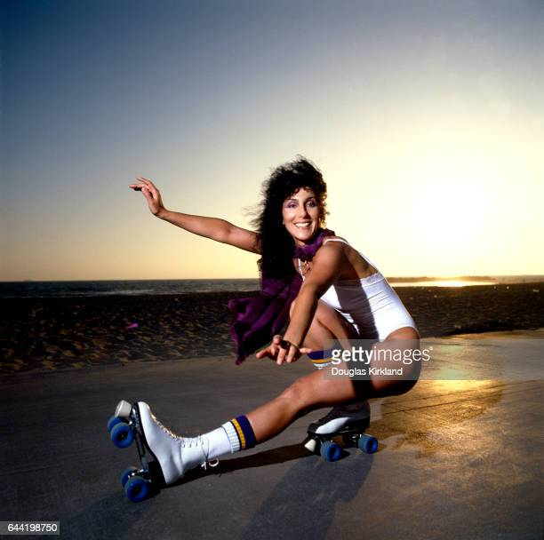 Singer and actress Cher wearing a white swimsuit shows off her roller skating moves at Venice Beach California