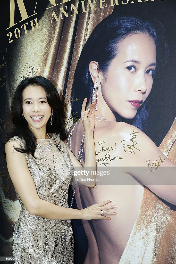 Singer and actress Karen Mok poses with a poster of herself at the openiing of the Karen Mok 20th Anniversary Exhibition at the Landmark building, Central on September 15, 2013 in Hong Kong, Hong Kong.