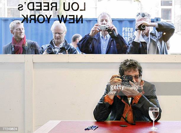 Singer and artist Lou Reed takes a pictures during the opening of his exhibition Lou Reed's New York in gallery Serieuze Zaken Studioos in Amsterdam...