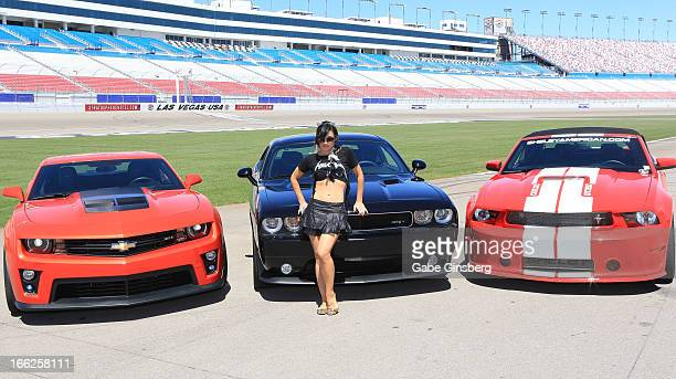 Singer and burlesque dancer Melody Sweets from the show 'Absinthe' poses in front of Chevrolet Camero ZL1 Dodge Challenger SRT8 392 and a Ford...
