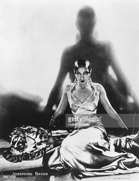 Singer and dancer Josephine Baker sitting on a tiger rug