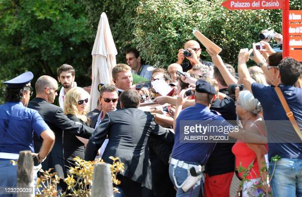 """Singer and film director Madonna signs autographs before boarding a motorboat while policemen block the crowd after the photocall of """"W.E."""" at the..."""