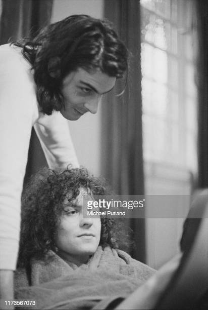 Singer and guitarist Marc Bolan , at bottom, and Mickey Finn of English glam rock group T Rex backstage viewing a fan's scrapbook of the band at...