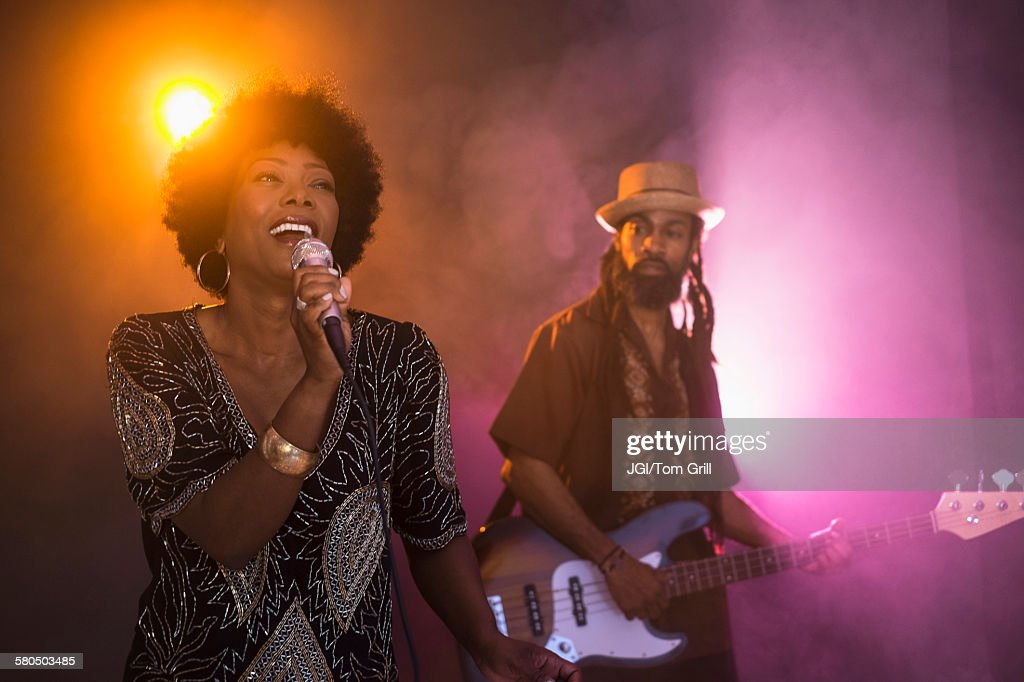 Singer and guitarist performing on stage : Stock Photo