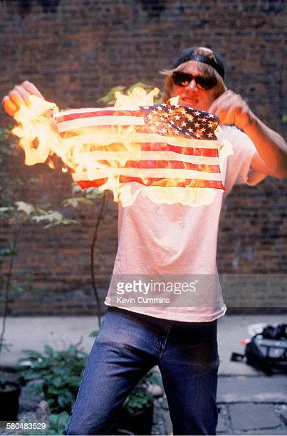 Singer and guitarist Thurston Moore of American alternative rock group Sonic Youth holding a burning stars and stripes New York City 17th June 1992