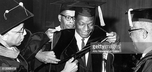 Singer and Jazz musician Nat King Cole receiving an honorary degree during a graduation ceremony 1953