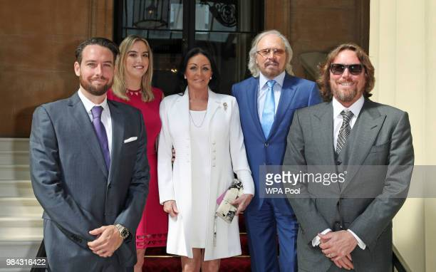 Singer and songwriter Barry Gibb poses for a photo with his wife Linda and children Michael Alexandra and Ashley ahead of being knighted during an...