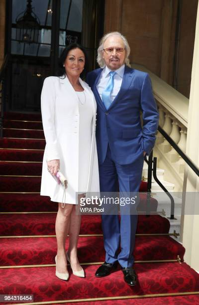Singer and songwriter Barry Gibb poses for a photo with his wife Linda ahead of being knighted during an investiture ceremony at Buckingham Palace on...