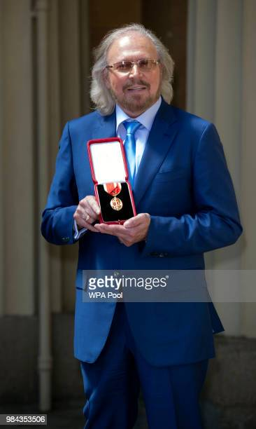 Singer and songwriter Barry Gibb poses for a picture after being Knighted by Prince Charles Prince of Wales during investitures at Buckingham Palace...