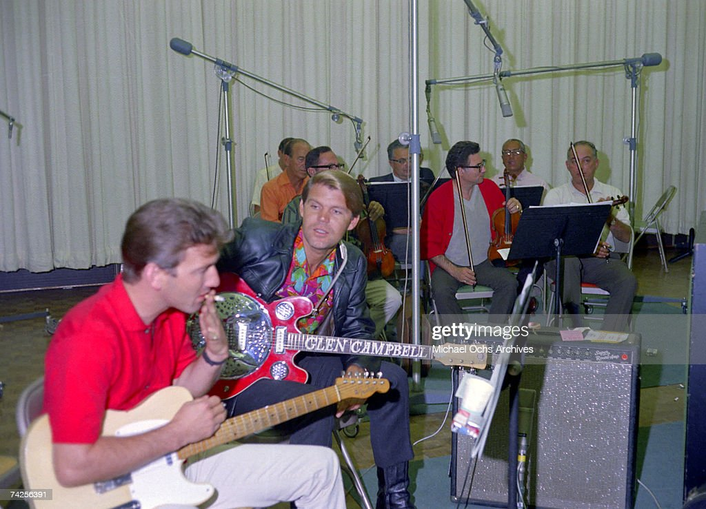 Singer and Songwriter Glen Campbell (R) and guitarist James Burton (L) record at the Columbia Records Studio on September 15, 1967 in Los Angeles, California.